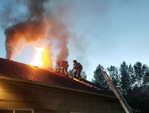 Fire District 7 firefighters battle flames on roof. Photo courtesy of Fire District 7.