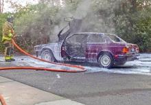 Fire District 1 firefighter extinguishes car fire on 35th Avenue SE. Photo credit: Mill Creek Police Officer Chris White.