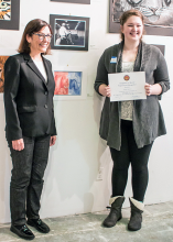Skylar Barrett (holding certificate) and Congresswoman Suzan DelBene stand next to the Barrett's watercolor art print representing the mascots of US political parties.